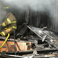 A Firefighter work to put out a blaze at Doggie Do's on Mobile Street in Saltillo on Wednesday afternoon.
