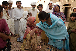 "Asia Perveen, a social worker with the Human Rights Commission in Multan, meets with the family of sisters Tasleem and Zubada, Dera, Pakistan, April 26, 2005. The two were gang raped by neighbors who felt they were dishonored by Zubada's son Naeem. ""I want them to be punished,"" said Tasleem. ""They are our enemies, I will be afraid until they are hanged publicly."""