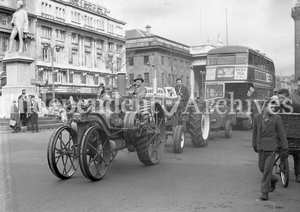 Tractors and a bus in view of the Metropole. Old farm machinery in O'Connell St. 1964 <br />