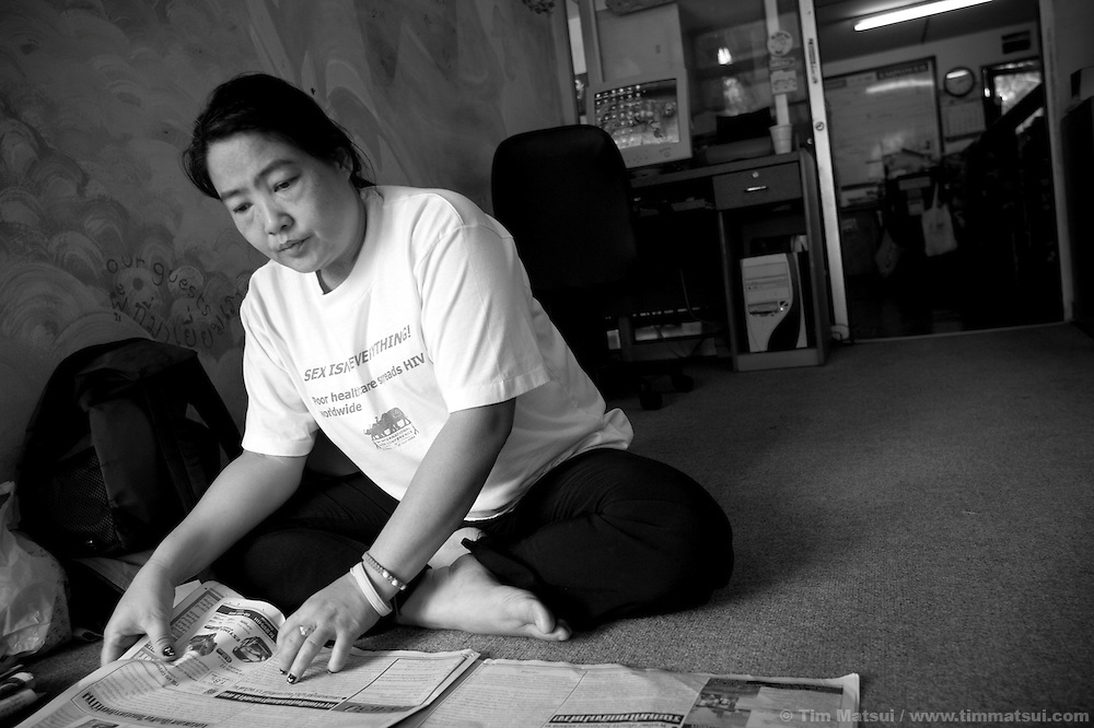 "ID: Noi reads the paper. >> At the Chiang Mai office of the Empower Foundation in northern Thailand, which serves as a drop-in center offering computer and informal English training, health education, counseling and other support to sex workers. Founded in 1985 the organization has five centers from Phuket to Mai Sai and advocates for recognition, equality, and basic human rights for sex workers in Thai society where sex work is common, visible, and yet illegal..>>.Empower Chiang Mai opened the ""Can-Do"" bar which offers fair working conditions to sex workers by complying with all Thai Labor Laws and the recommended occupational health and safety standards..>>.Empower, which works with women over 18 years-old and is a vocal opponent of human trafficking, sexual or labor exploitation of any person,  is also campaigning to change the methods of anti-human trafficking groups. Empower states ""the focus on trafficking in persons has meant many groups with little or no experience on the issues of migration, labor, sex work or women's rights have been created to take advantage of the large sums of money available to support anti-trafficking activities."".>>.Recommendations by sex workers, many who were Burmese, some who had been trafficked, and all who acknowledged enlisting an agent to migrate illegally into Thailand, stated among other things that ""The primary goal of prosecuting traffickers must be altered to a primary goal of assisting trafficked women and children...if trafficked women and children...are continually rescued and assisted, the use of trafficked women and children will become unprofitable...we are willing to work our illegal status leaves us with no recourse against exploitation by agents or employers...Anti-trafficking groups must work toward improving the human rights situation...Anti-trafficking dialogue and groups have yet to consider us as anti-trafficking workers and human rights defenders...The latest stance from the USA government calling us ""inapp"