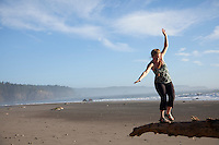 Young woman balancing on log near Third Beach in Olympic National Park, WA