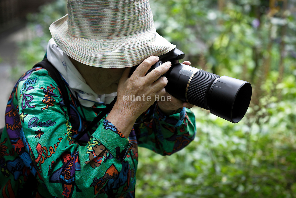 elderly woman taking pictures in a public garden