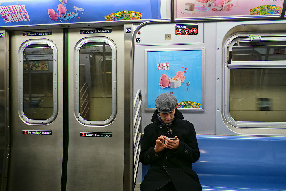 "Subway rider with iPhone under ""Multiply your money"" ad, New York, NY, US"