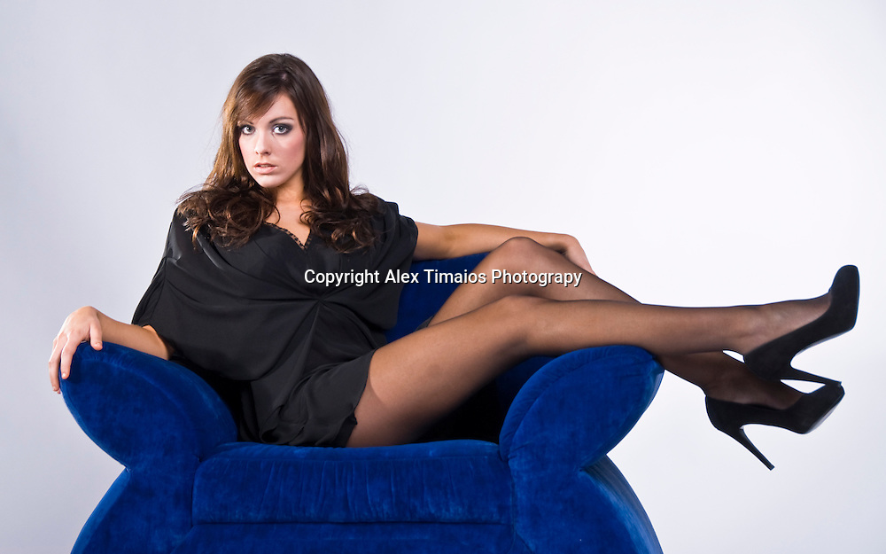 Young lady in mini dress sitting on a blue sofa