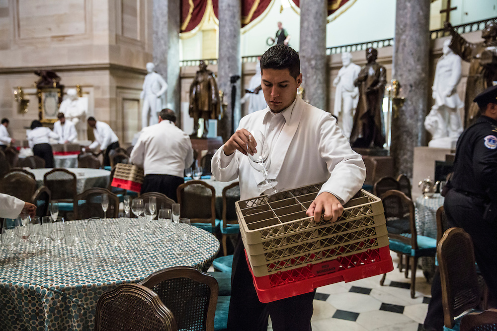 A catering employee cleans up glasses following the Inaugural Luncheon in Statuary Hall at the U.S. Capitol on Monday, January 21, 2013 in Washington, DC.
