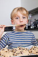 Portrait of young boy tasting spatula mix with cookie batter