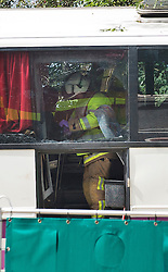 © London News Pictures. 11/09/2012. Hindhead, UK . A fire crew on board the bus at the scene of a fatal bus crash on the north bound A3 motorway near Hindhead Tunnel, Hindhead, Surrey on September 11, 2012.Three people were killed and a number of others seriously injured when a coach carrying overturned after crashing into a tree. Photo credit: Ben Cawthra/LNP