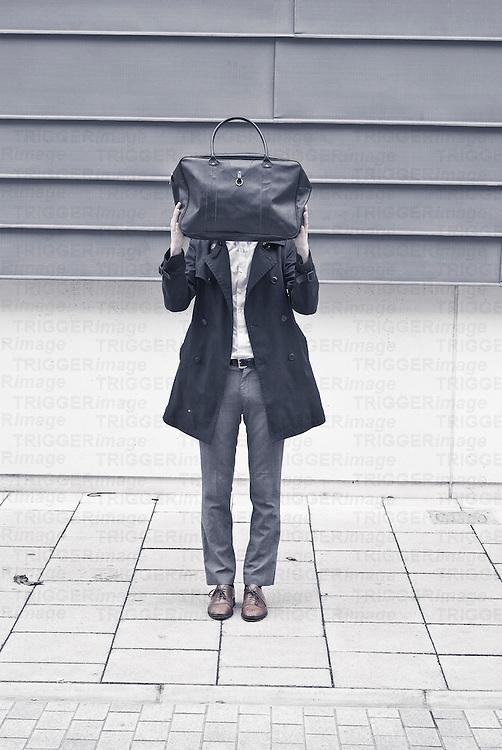 A man standing on a street hiding behind a bag