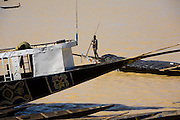 "A man drives a ""pinasse"" in the harbour of Mopti. At the confluence of the Niger and the Bani rivers, between Timbuktu and Segou, Mopti is the second largest city in Mali, and the hub for commerce and tourism in this west-african landlocked country."