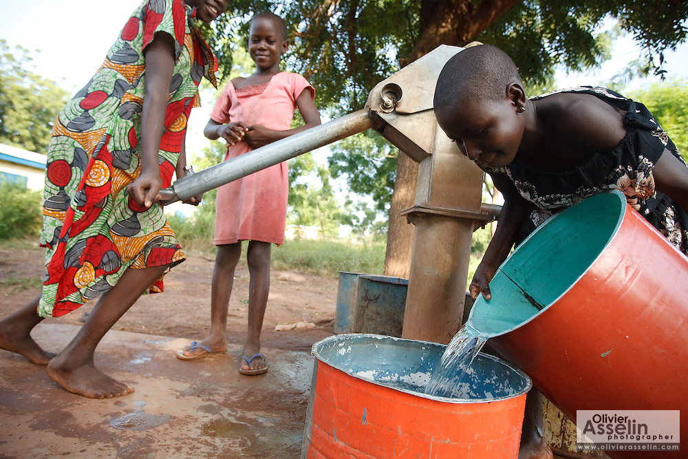 A girl pours water from one bucket into  another after getting water from a handpump in the village of Moglaa, Ghana on Thursday November 11, 2010.