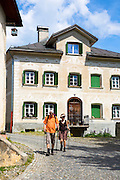 Tourists in the Engadine Valley village of Guarda with old painted stone 17th Century buildings, Switzerland
