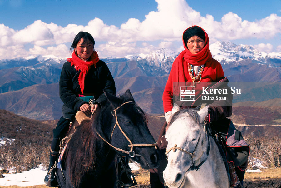 Two Tibetan girls on horseback, snow-capped mountains at back, Nine Village Valley, Sichuan Province, China