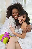 Young woman embracing friend at bridal shower
