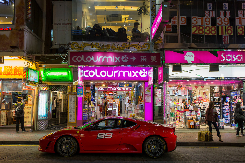 A red Ferrari parked outside a Colourmix shop on Lockhart Road, Causeway Bay, Hong Kong. (photo by Andrew Aitchison / In pictures via Getty Images)