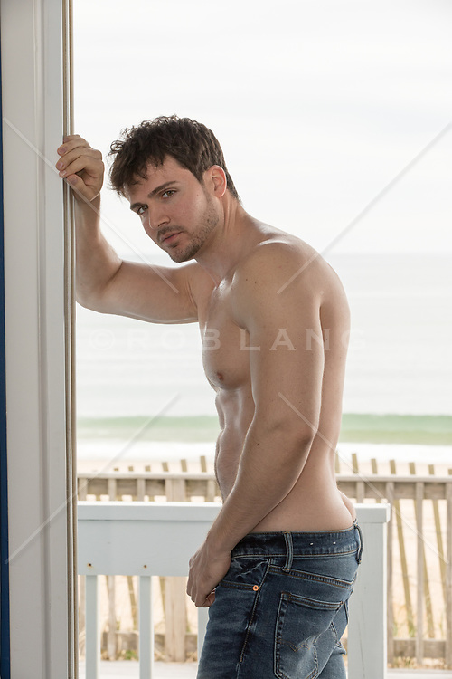 shirtless hot man in a doorway by the sea