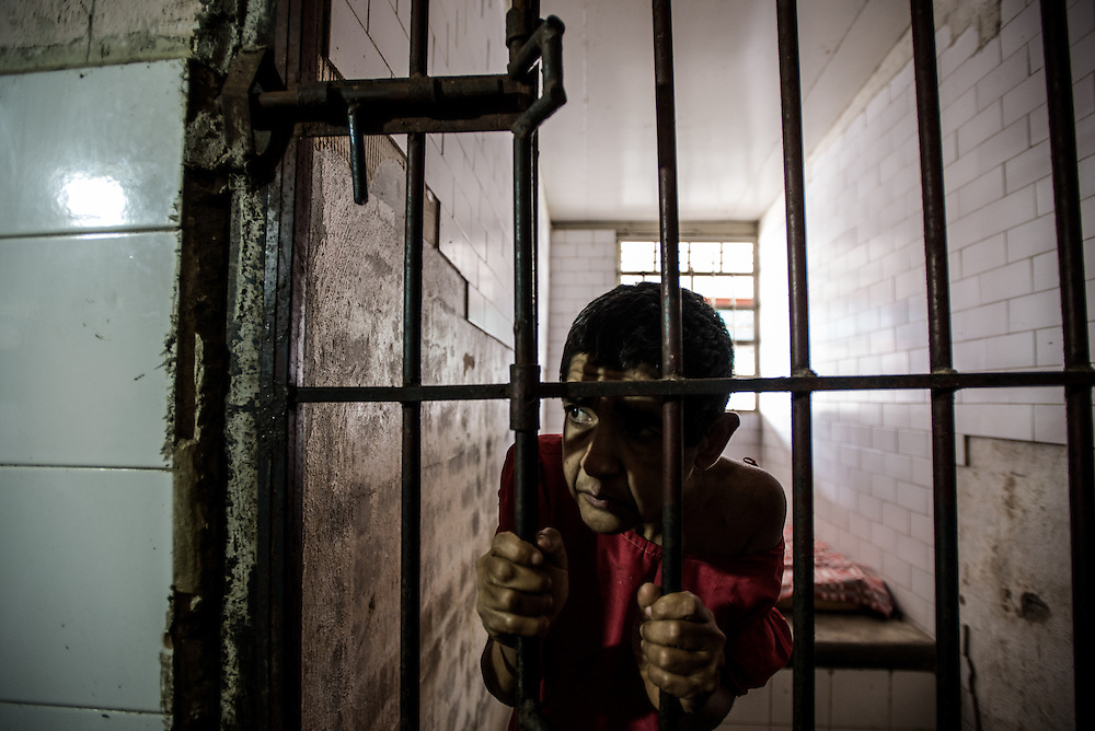 BARQUISIMETO, VENEZUELA - JULY 28, 2016: Iris Rodríguez, a patient who suffers from organic psychosis and mental retardation, and who was abandoned by her family, looks through the bars of her solitary confinement cell. Iris spends most of her time sitting, rocking back and forth and very rarely speaks. She is not violent, but the nursing staff keeps her locked in isolation because she eats things that she shouldn't when she is left to roam around the women's ward and patio with other patients. The economic crisis that has left Venezuela with little hard currency has also severely affected its public health system, crippling hospitals like El Pampero Psychiatric Hospital by leaving it without the resources it needs to take care of patients living there, the majority of whom have been abandoned by their families and rely completely on the state to meet their basic needs. PHOTO: Meridith Kohut