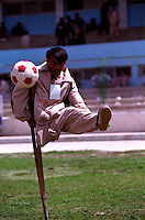 KABUL 24 August 2005.A disable athlete plays football while holding himself on a crutch...On 23-25 August 2005, Special Olympics Afghanistan held its first national Games at Olympic Stadium in Kabul. .More than 300 athletes, including 80 female athletes, experienced a taste of happiness and achievement for the first time in their lives. They competed in athletics, bocce and football (soccer). Because of cultural restrictions, males and females competed at separate venues..