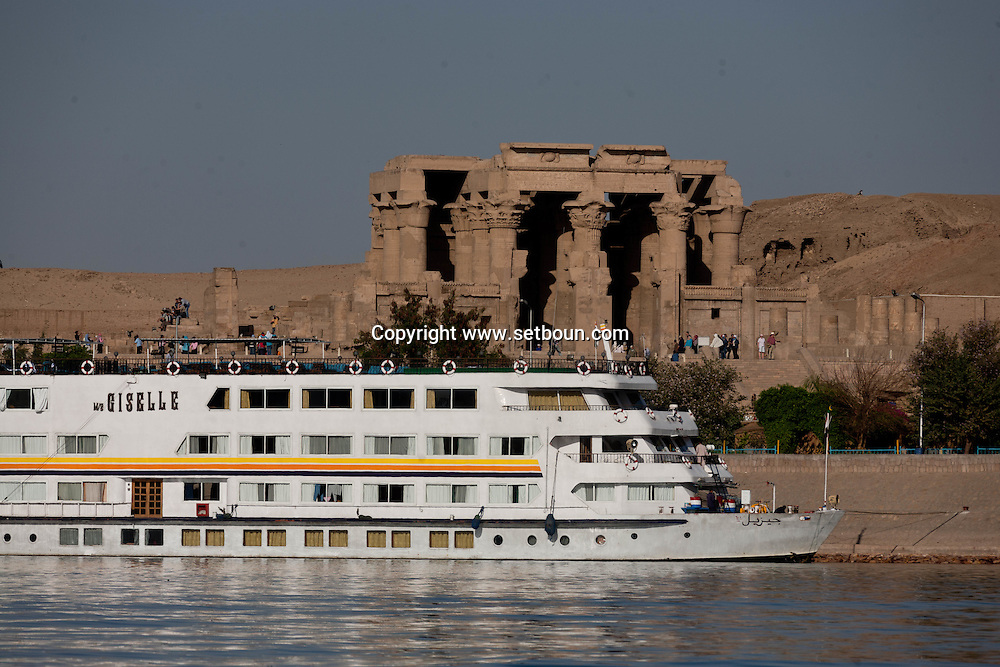 Egypt. Louxor - cruise on a Sandal  boat in front of Kom Ombo temple   traditional boat transformed in a cruise boat)  on the Nile river near  Kom Ombo  Egypt    /  croisiere sur le Nil sur un Sandal, Bateau tradionnel sur le  Nil devant  le temple de Kom Ombo  . dedie à Sobek le crocodile et Haroeris .  Kom Ombo  Egypte   /  L0056029