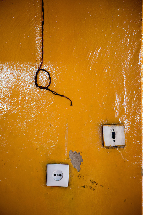 """Aged walls and weathered light switches are seen in the Gandantegchinlen Monastery, known as the Gandan Monastery, a Tibetan-style monastery in the Ulaanbaatar Mongolian, on July 23, 2012.  The Tibetan name translates to the """"Great Place of Complete Joy."""" It features a 26.5-meter-high statue of Migjid Janraisig, a Buddhist bodhisattva also known as Avalokitesvara.  It currently has over 150 monks in residence. The Gandan Monastery was renovated in 1990 following the collapse of the communist government in Mongolia. © 2012 Tom Turner Photography."""