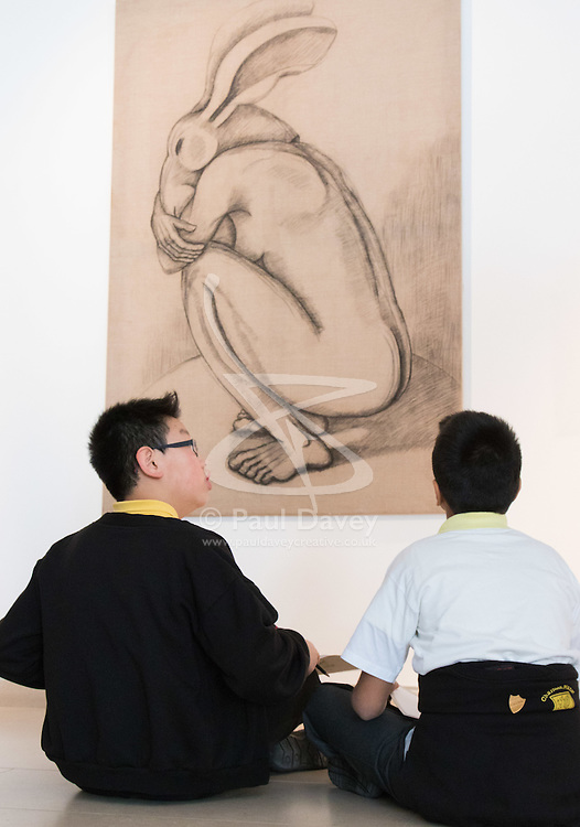 """Christies, St James, London, March 4th 2016. Two boys from Charlton Manor Primary School draw Sophie Ryder's charcoal on Linen """"Crouching Figure"""", 2006, at the preview for the It's Our World charity auction at Christie's. Over 40 leading artists including David Hockney, Sir Antony Gormley, David Nash, Sir Peter Blake, Yinka Shonibare, Sir Quentin Blake, Emily Young and Maggi Hambling have committed artworks to the It's Our World Auction in support of The Big Draw and Jupiter Artland Foundation, to be sold at Christie's London on 10 March 2016.<br />  ///FOR LICENCING CONTACT: paul@pauldaveycreative.co.uk TEL:+44 (0) 7966 016 296 or +44 (0) 20 8969 6875. ©2015 Paul R Davey. All rights reserved."""