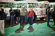 28 NOVEMBER 2006 - SAN LUIS, AZ: Farm workers wait to board busses to go to work in fields near San Luis, AZ, about 20 miles south of Yuma. Farmers and agricultural producers around Yuma, AZ, are facing a growing shortage of farm workers. Increased border enforcement have deterred many illegal workers from seeking work in Arizona and long lines at the ports of entry for legal workers are leading to the labor shortage. Some labor contractors are reporting as much as a 40 percent shortage of farm workers, Yuma farmers planted 15 percent fewer acres this year, compared to last, because of the shortage. More than 100,000 acres of iceberg lettuce are cultivated in Yuma county and more than 50,000 people are employed as seasonal farm workers at the height of the harvest, which is December through February. Nearly 3,500 seasonal farm workers stand in line for up to two hours every morning at the San Luis, AZ, Port of Entry to enter the US legally to work in the fields. Experienced workers can make as much as $14 (US) per hour during the harvest.  Photo by Jack Kurtz