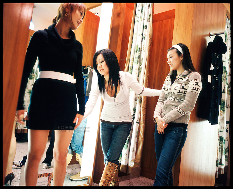 Aritzia employees assist a customer in the store's fitting room.