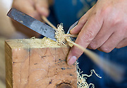 Ichiro Iwao uses a v-shaped cutting implement known as a habatori-kogatana, through which he draws lengths of bamboo to ensure they are all of equal width at Iwao Chikuran's workshop in Beppu City, Oita Prefecture, Japan on Sept. 20. 2016.  ROB GILHOOLY PHOTO