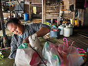 05 OCTOBER 2015 - BANGKOK, THAILAND: A worker packs out a resident's posessions on moving day in the Wat Kalayanamit neighborhood. The people moving were being evicted from their homes. Fifty-four homes around Wat Kalayanamit, a historic Buddhist temple on the Chao Phraya River in the Thonburi section of Bangkok, are being razed and the residents evicted to make way for new development at the temple. The abbot of the temple said he was evicting the residents, who have lived on the temple grounds for generations, because their homes are unsafe and because he wants to improve the temple grounds. The evictions are a part of a Bangkok trend, especially along the Chao Phraya River and BTS light rail lines. Low income people are being evicted from their long time homes to make way for urban renewal.        PHOTO BY JACK KURTZ