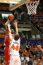 02 January 2004 Marcus Arnold mounts an attack over the tall arms of Augustine.  Illinois State University ties up The Fightin Illini in regulation but fails to top the Big 10 team in overtime. Action took place at the Assembly Hall on the University of Illinois Campus in Champaign - Urbana Illinois.