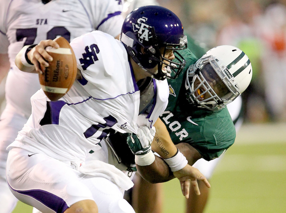 Stephen F. Austin quarterback Dalton Williams (14) is sacked near the goal line by Baylor defensive end Gary Mason, Jr. during an NCAA college football game, Saturday, Sept. 17, 2011, in Waco, Texas. Baylor won 48-0.