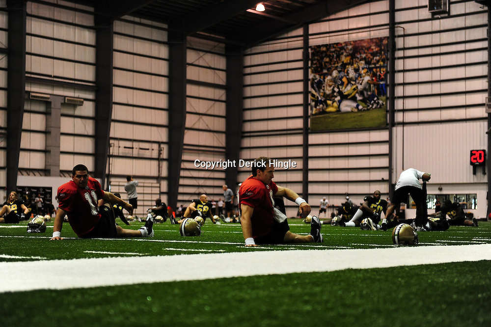 July 30, 2010; Metairie, LA, USA; New Orleans Saints quarterback Drew Brees (9) stretches with teammates during a training camp practice at the New Orleans Saints indoor practice facility. Mandatory Credit: Derick E. Hingle