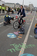 A commuter cycles past Climate Change activists with Extinction Rebellion campaigning for a better future for planet Earth after blocking Waterloo Bridge and as part of a multi-location 5-day Easter protest around the capital, on 16th April 2019, in London, England.