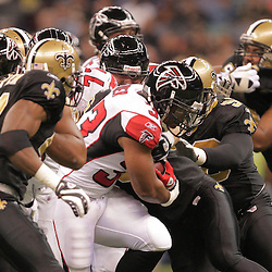 2008 December, 07: A host of New Orleans Saints defenders close in for a tackle on Atlanta Falcons running back Michael Turner (33) during a 29-25 victory by the New Orleans Saints over NFC South divisional rivals the Atlanta Falcons at the Louisiana Superdome in New Orleans, LA.