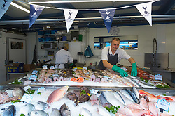 James Pledger, 45, at Thompson's seafood in Holcombe Market, Tottenham with Spurs bunting adoring his  workplace ahead of Tottenham's Champions League final with Liverpool to be played at Atletico Madrid's Wanda Metropolitano Stadium in Madrid. Tottenham, London, May 31 2019.