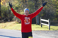 Goshen, New York  - A man raises his arms while running in the Hambletonian Marathon on Sunday, Oct. 20, 2013.