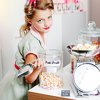 Young girl scooping candy onto a scale in a candy store. She is dressed in a 1950's dress, wears bright red lipstick and has a pretty red bow in her hair.