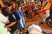 """Oct. 2, 2009 -- BANGKOK, THAILAND: Volunteers from the Poh Teck Tung Foundation and members of the public gather around the scene of a fatal motorcycle accident in Bangkok, Thailand. The 1,000 plus volunteers of the Poh Teck Tung Foundation are really Bangkok's first responders. Famous because they pick up the dead bodies after murders, traffic accidents, suicides and other unplanned, often violent deaths, they really do much more. Their medics respond to medical emergencies, from minor bumps and scrapes to major trauma. Their technicians respond to building collapses and traffic accidents with heavy equipment and the """"Jaws of Life"""" and their divers respond to accidents in the rivers and khlongs of Bangkok. The organization was founded by Chinese immigrants in Bangkok in 1909. Their efforts include a hospital, college tuition for the poor and tsunami relief.    Photo by Jack Kurtz / ZUMA Press"""