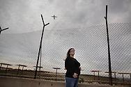 Lampedusa, Italia - Rossana Maggiore (incinta di 7 mesi) ritratta nei pressi dell'aeroporto di Lampedusa mentre decolla un aereo. Le donne lampedusane in attesa sono costrette a far nascere i propri figli lontano da Lampedusa a causa della mancanza di strutture attrezzate al parto. Fra nascere un bambino costra tra i seimila e i diecimila euro. Le donne dunque, arrivate al settimo mese, lasciano l'isola per trasferirsi in ospedali attrezzati a Palermo, Catania, Torino. Il tutto senza alcun rimborso spese.<br /> Ph. Roberto Salomone
