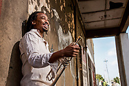 young man with his trumpet leaning on a wall