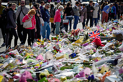 © Licensed to London News Pictures. 30/03/2017. London, UK. Member son the public look over carpet of floral tributes left outside the Houses of Parliament in London, following a terrorist attack last week. 52-year-old Briton Khalid Masood drove a car at pedestrians on Westminster Bridge before stabbing to death PC Keith Palmer while attempting to enter Parliament. Photo credit: Ben Cawthra/LNP