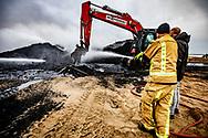 SCHEVENINGEN - Brandweer bezig met nablussen de dag na de vonkenregen bij de boulevard van Scheveningen die ontstond door het vreugdevuur op het strand. Door de wind waaide er vliegvuur over het strand er door de straten.  Door de lucht vliegende vonken van het grote vreugdevuur op het strand bij Scheveningen hebben in de omgeving meerdere branden veroorzaakt. De boulevard van Scheveningen is ontruimd omdat het vreugdevuur te groot is geworden.