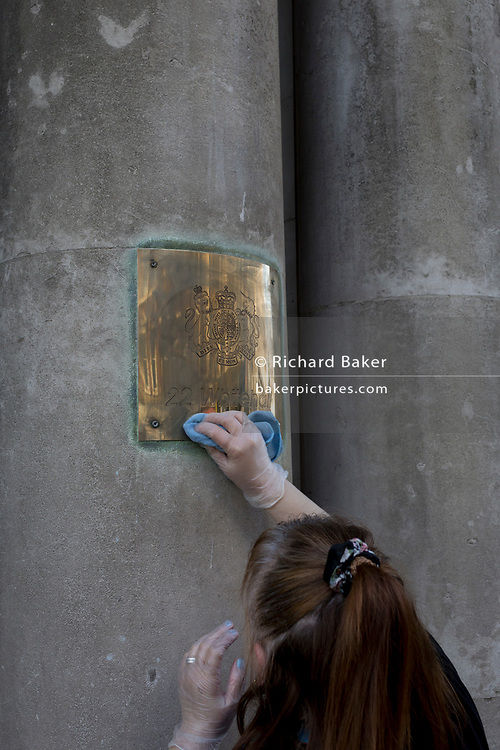 A cleaner polishes the brass nameplate at the entrance to the Department for International Development, Kirkland House, 22 Whitehall, on 13th November 2018, in London, England.