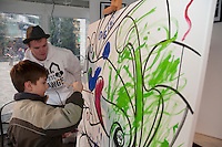 Stan Matwychuk, artist, paints with a young guest during the Whistler Live events in Whistler Village during the 2010 Winter Olympic Games.