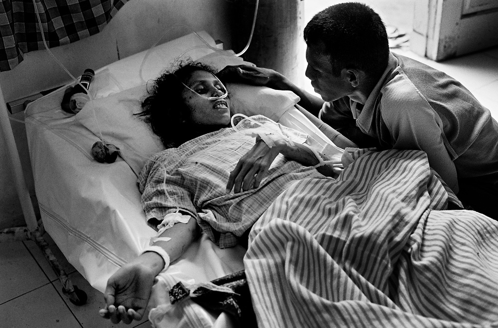 A man comforts his seriously ill wife at Kesdam Military hospital. Having survived a decades old  war between the Indonesian Military and GAM, Aceh is struck by a Tsunami on December 26th, 2004, claiming the lives of thousands.