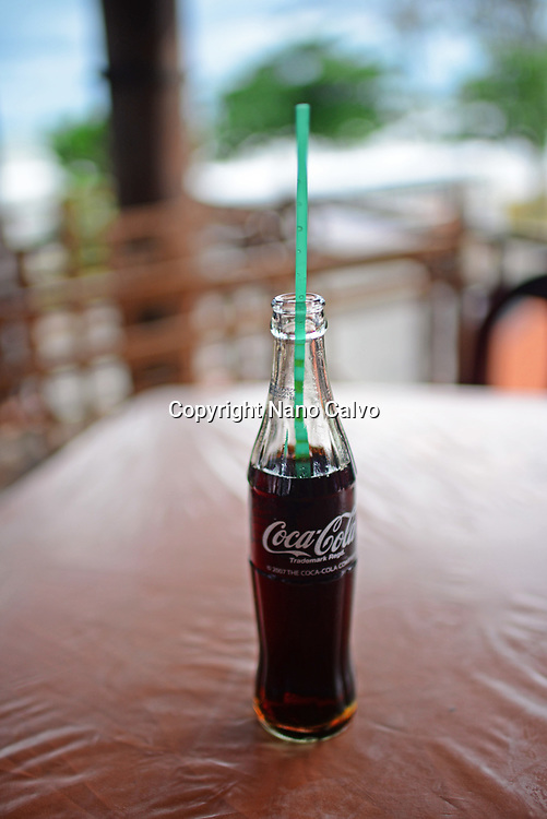 CocaCola bottle with a straw on restaurant table, Sri Lanka