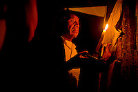 A elderly man uses a candle to illuminate a young family member who was found dead from hanging himself in his bedroom late in the night of Zone 7 in  Guatemala city Sunday Oct. 29, 2007 in Guatemala. .             ..........