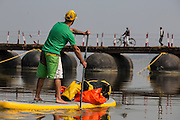 Jay paddles up toward a pontoon bridge across the Ganga.