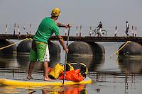 Jay paddles up toward a pontoon bridge across the Ganga.