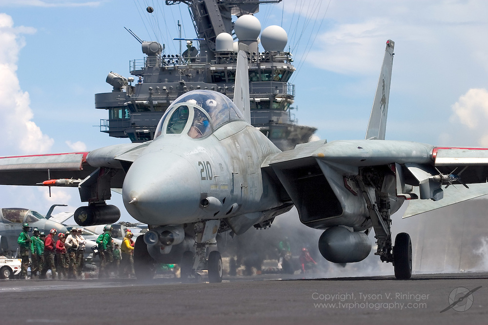 In its crouched position, an F-14 Tomcat from VF-213 'Blacklions', AJ210, accelerates off the deck of the USS Theodore Roosevelt CVN-71 during sea trials prior to their 2005 Mediterranean deployment. This would be the final cruise for the F-14 Tomcat and the last time it would ever see combat.