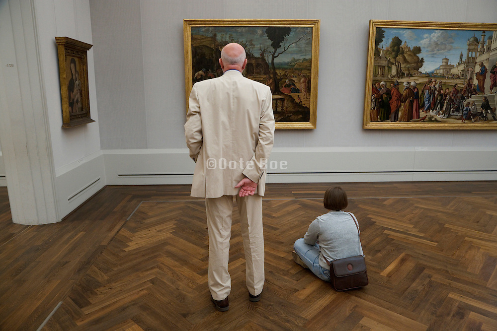 elderly person and young adult person looking at old painting is the Gemalde Gallerie Museum in Berlin